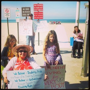 """At Pere Marquette, Advocates distribute flyers hold signs supporting consumer control at Disability Network West Michigan - signs say """"Independent Living is for Every Body,"""" """"We believe in Disability Pride,"""" etc."""