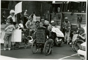 ADAPT activists protesting for accessible transportation, Philadelphia, 1990 - Signs read I Can't Even Get to the Back of the Bus and We Will Ride