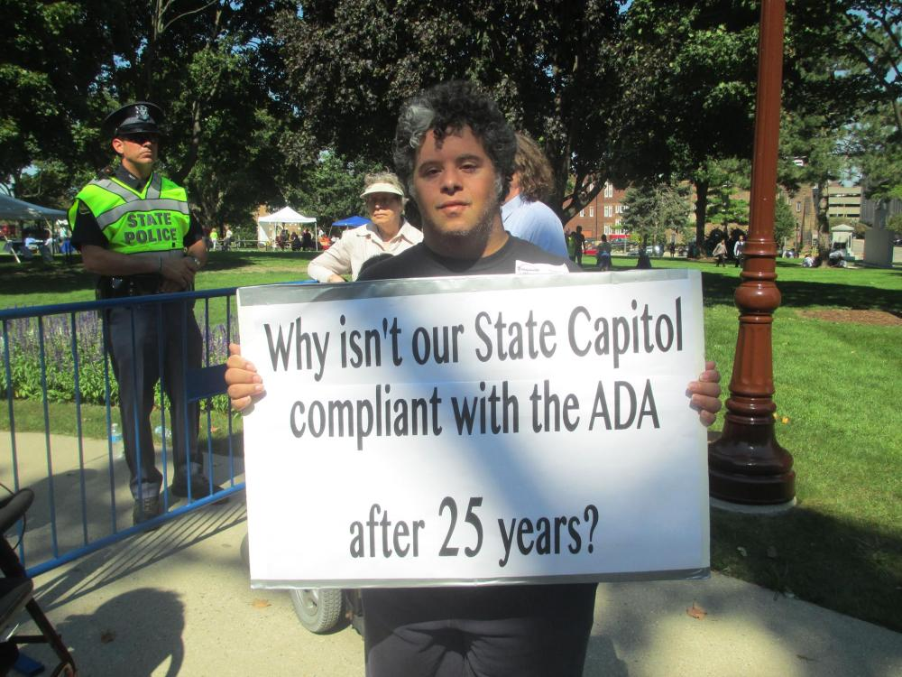 Man holding up sign that reads Why isn't our State Capitol compliant with the ADA after 25 years